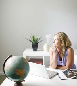 Woman sitting in home office and looking pensive